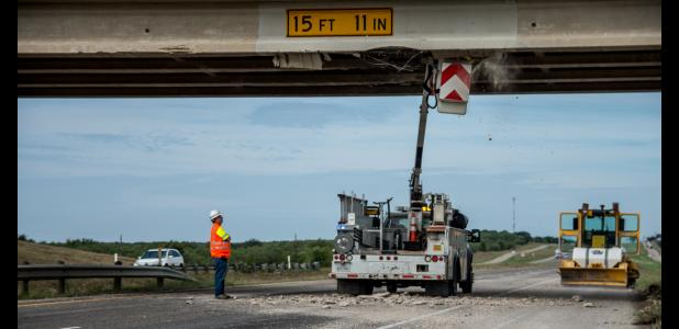 Crews assess damage and remove loose debris from the damaged support struts on the overpass.